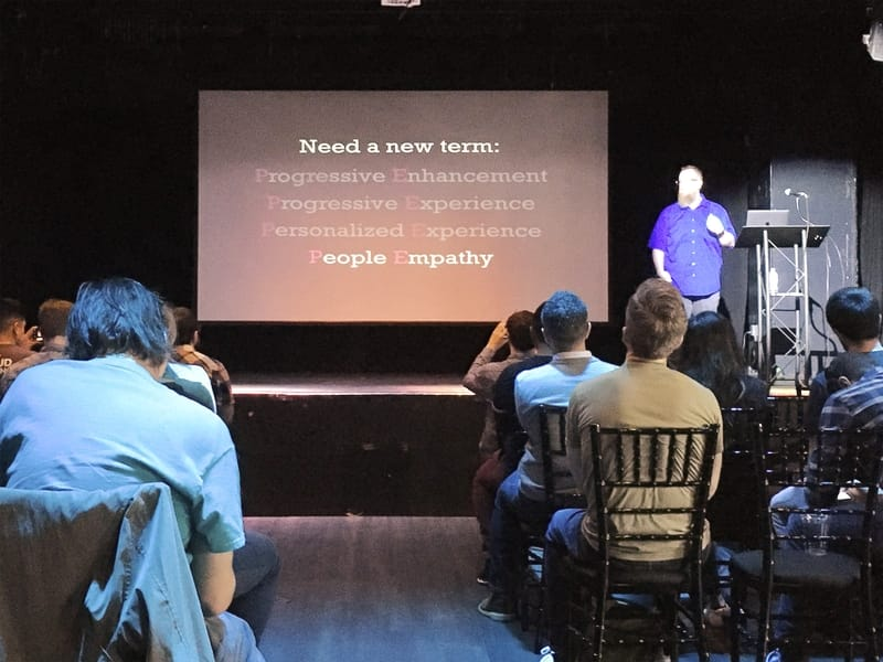"Kyle Simpson at Flashback Conference 2020 in Orlando. Slide reads, ""Need a new term: Progressive Enhancement, Progressive Experience, Personalized Experience, People Empathy"", with all options dimmed except for People Empathy"